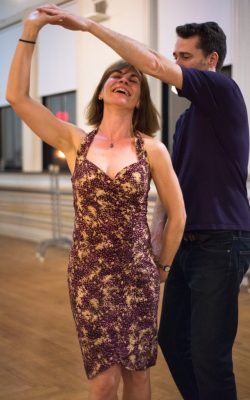 A woman smiles and laughs as her male salsa partner turns her around