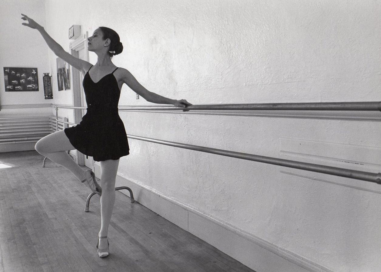 a female ballet dancer releves at the barre