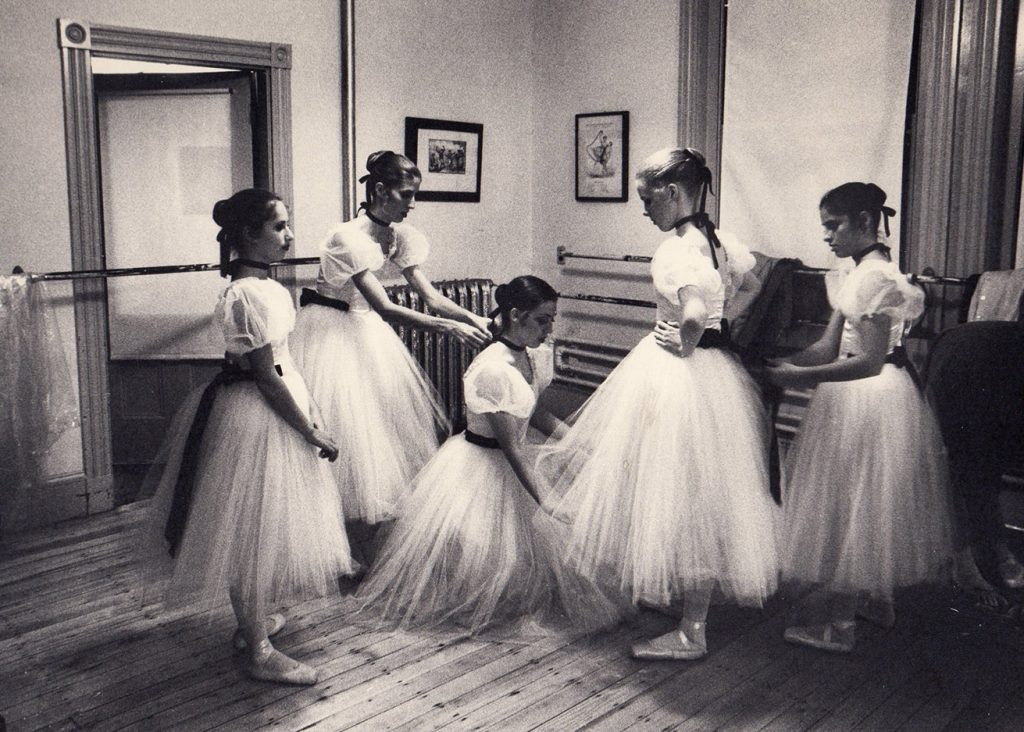 5 ballerinas prepare to go on stage in traditional long tutus
