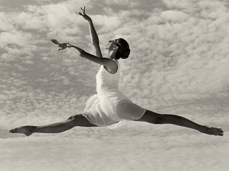A graceful dancer is captured mid leap with only sky and clouds behind her