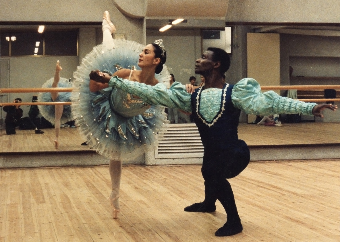 male dancer dressed as a prince presents his princess ballerina in her tutu and pointe slippers
