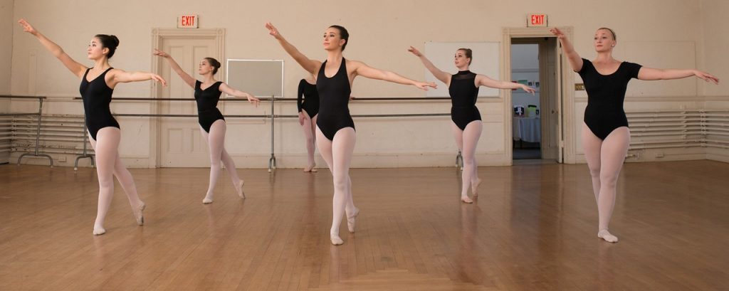 5 female dancers in black leotards and pink tights pose in arabesque