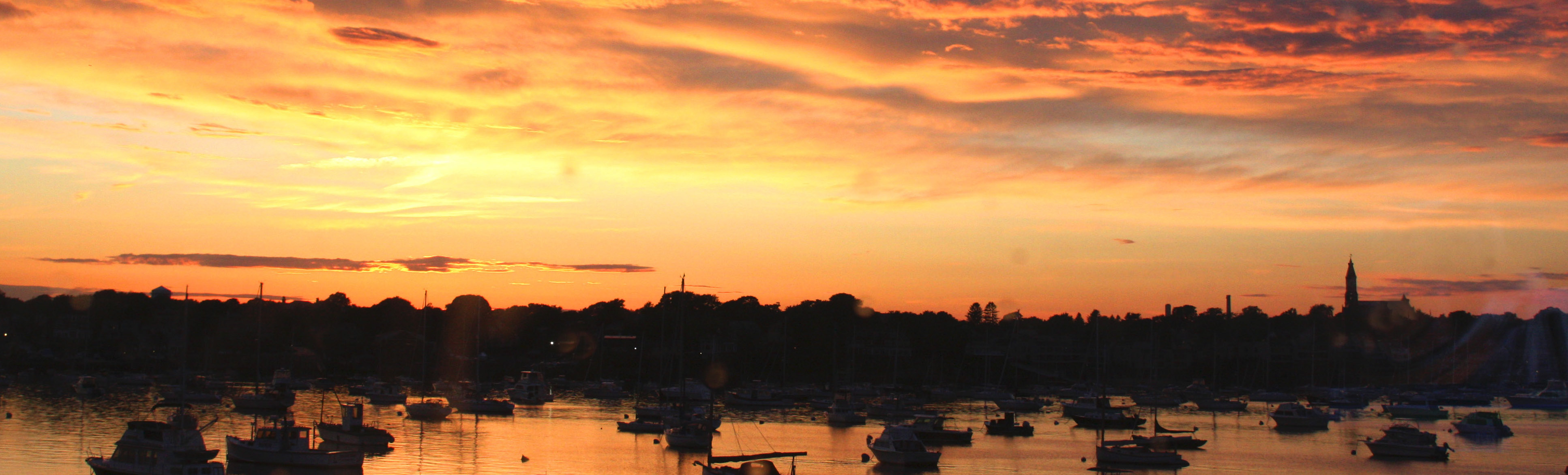 An orange sky stretches over the black silhouette of the Marblehead shore