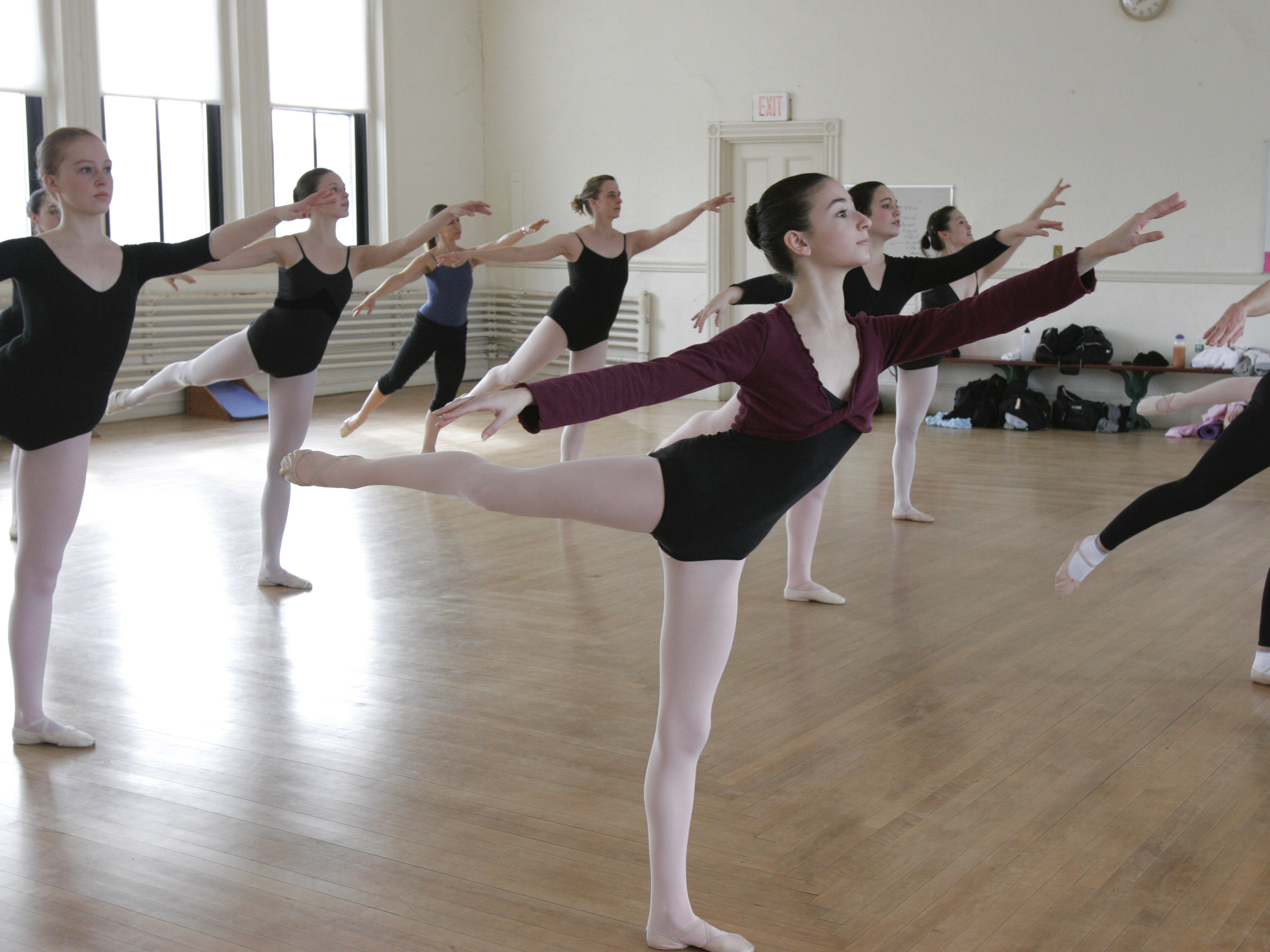 Dance studio full of ballet students pose in Arabesque