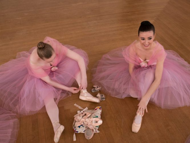 2 girls in traditional tutus lace up their pointe shoes